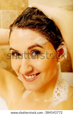Young happy woman washing hair in bath - stock photo