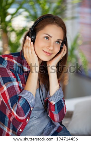 Young happy woman wearing headphones - stock photo
