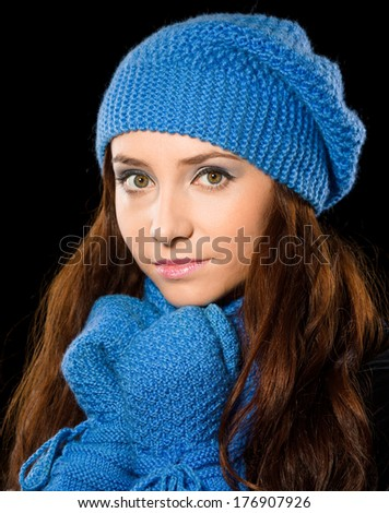 Young happy woman wearing winter cloth, isolated over black