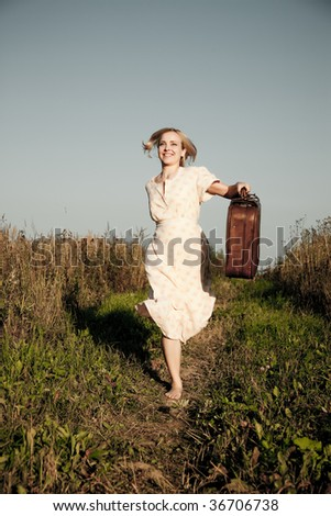 Young happy woman with a suitcase running on a rural road.