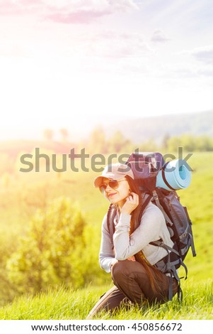 Young happy woman with backpack resting on green hill in sunrise beams. Beautiful traveling backpacker background with copy space - stock photo