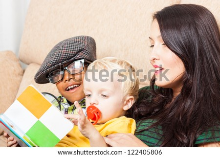 Young happy woman with children reading book. - stock photo