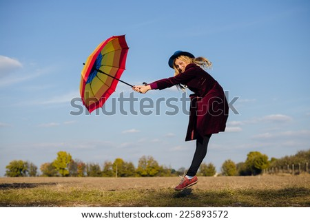 Young happy woman with colorful umbrella jumping funny on empty autumn field copy space background - stock photo