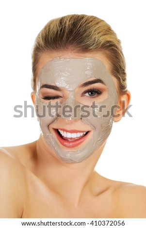 Young happy woman with facial mask. - stock photo