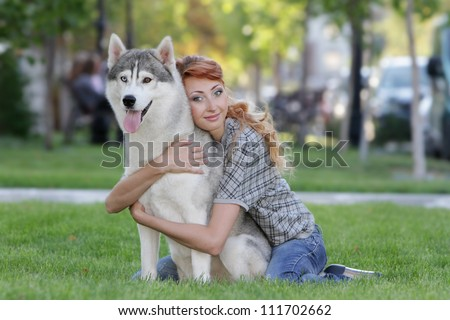 young happy woman with haski dog outdoors - stock photo