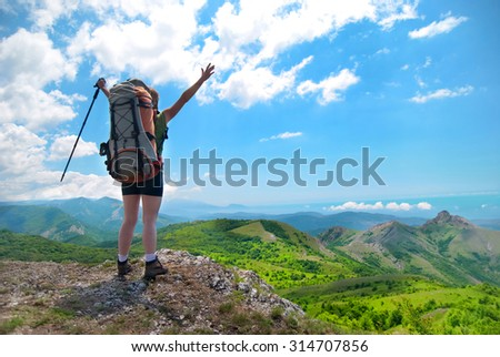 Young happy woman with hiking stick, backpack standing on the rock with raised hands and looking to green landscape  - stock photo