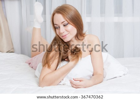Young happy woman with long hair enjoying lying in bed.