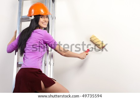 Young happy woman with paint roller in new house - stock photo