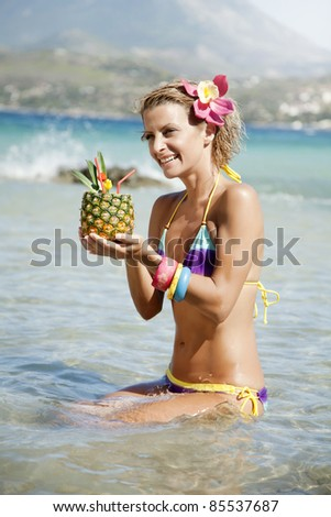 young happy woman with pineapple cocktail in exotic destination - stock photo