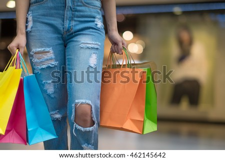 young happy woman with shopping bags over mall background