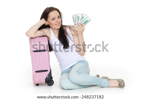 Young happy woman with suitcase and money sits on a white background. Vacation. - stock photo
