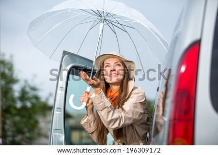 Young happy woman with umbrella go from car.  Happy car traveler concept - stock photo