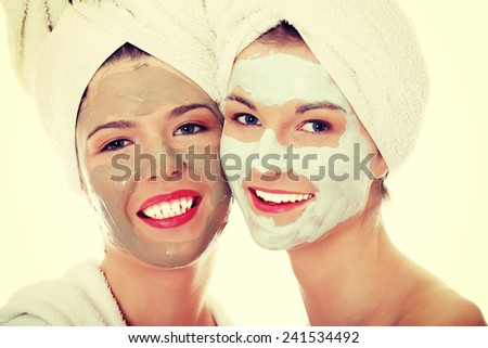 Young happy women with facial clay mask. - stock photo