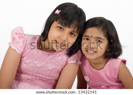 Young happy young Asian sisters in pink dress at play - stock photo