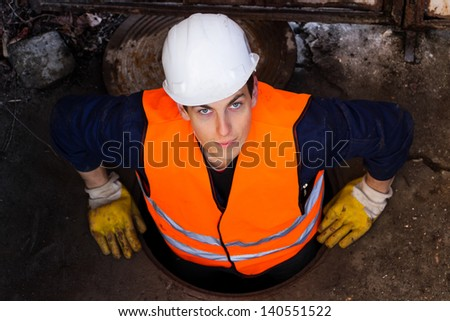 Young hard worker in his protective clothing going out from the sewage and looking directly at the camera.  Serbia. - stock photo