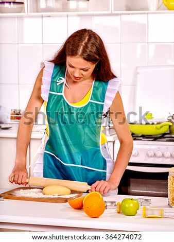 Young hardworking woman cooking at kitchen.