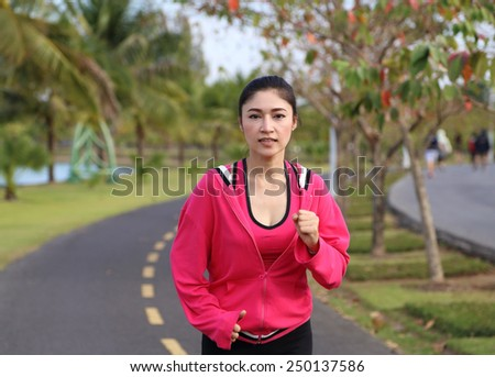 young healthy asian woman running in the park - stock photo
