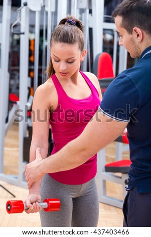 Young, healthy, attractive adult girl performing biceps muscle workout with professional, personal instructor / trainer at the gym with motivation. - stock photo
