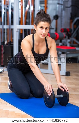 Young, healthy, attractive, caucasian athlete girls portrait while resting on a mat with a dumbbell under her hands at the gym. - stock photo