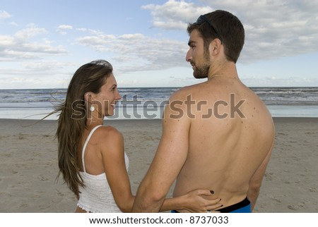 Young healthy couple looking at each other in the beach. - stock photo