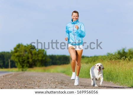Young healthy girl running outdoor with her dog - stock photo