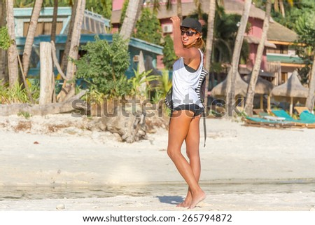 young healthy girl, woman, in sport clothes walking by tropical beach, outdoor portrait - stock photo