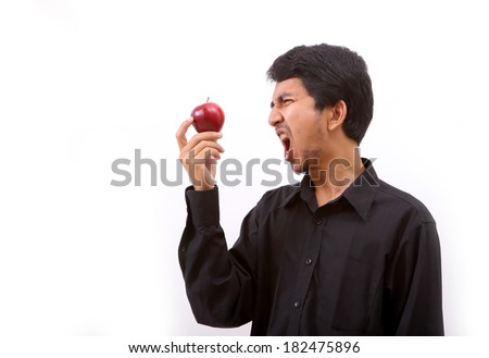 Young healthy man eating a red apple on white background