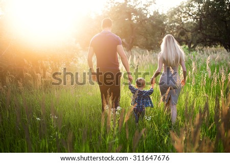 Young healthy parents mom and dad holding his son's hand, embrace and walk together outdoors in sunset light, family, lifestyle, happiness, love, the future - stock photo