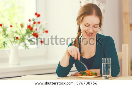 young healthy woman eats vegetables at home in the kitchen summer - stock photo