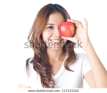 Young healthy woman holding red apple over her eyes on white background - stock photo