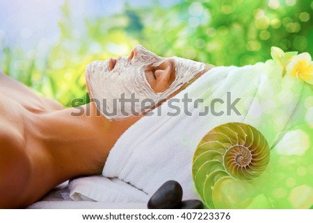 Young healthy woman in tropical spa making treatments and face mask