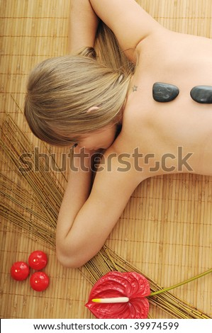 young healthy woman in wellness and spa studio have Massage with hot volcanic stones - stock photo