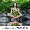 Young healthy woman meditating in the forest - stock photo