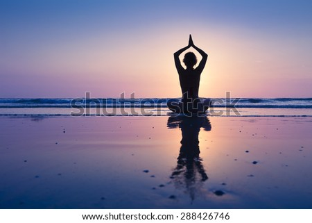 Young healthy woman practicing yoga on the beach - stock photo