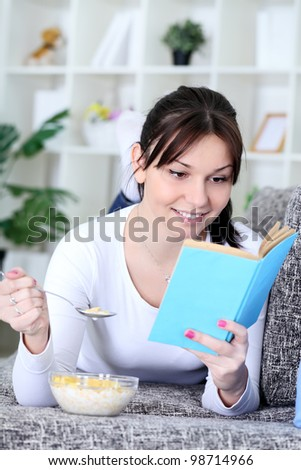 Young healthy woman reading book and eating snack - stock photo