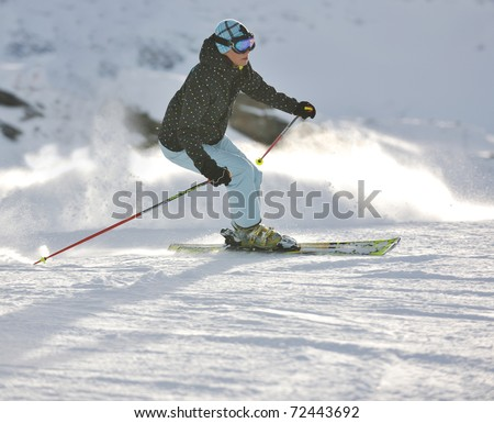 young healthy woman skiing on fresh snow at winter season in france alps - stock photo