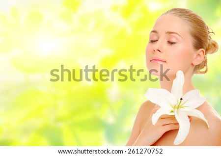 Young healthy woman with flower on spring background - stock photo