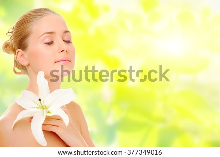 Young healthy woman with flower on spring background