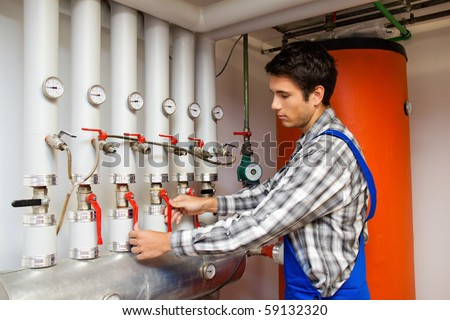 Young heating engineer in a boiler room for heating system - stock photo