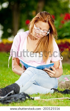 young high school student or college girl learn and sit in the park on the green grass/young high school studen - stock photo