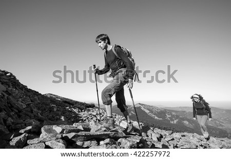 Young hiker couple climbing up rocky the mountain top, high altitude. Beautiful mountain landscape on the background. black and white - stock photo