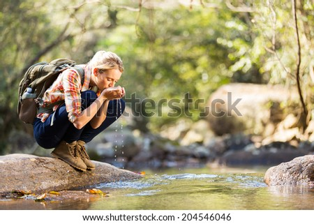 young hiker drinking stream water in mountain - stock photo