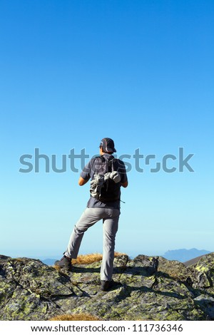 Young hiker enjoying the view from the top of the mountains - stock photo