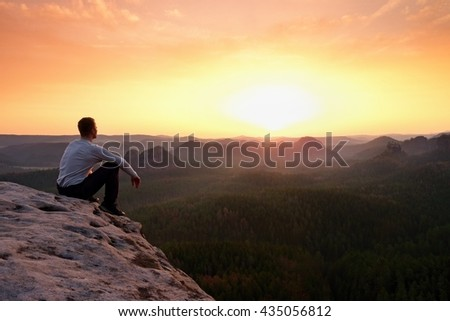 Young hiker in black trousers and grey shirt  sit on cliff's edge. Tourist watching sunrise above  misty hilly valley bellow mountain
