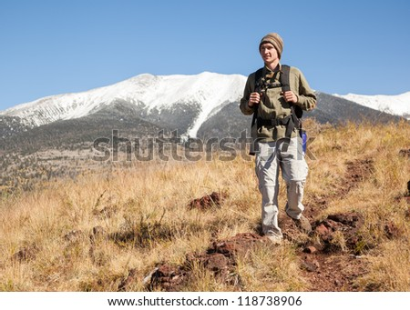Young hiker on mountain footpath with snow-capped mountain in background. (Humphrey's Peak in Flagstaff, Arizona) - stock photo