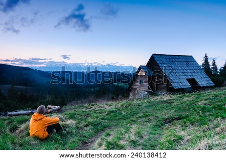 Young hiker relaxing in front of beautiful mountain hut with view on sharp peaks of High Tatras in the background after exhausting trek - stock photo