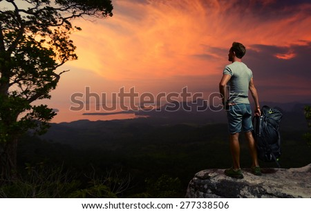 Young hiker standing on the rock and enjoying bright tropical sunset - stock photo