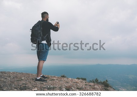 Young hiker taking picture with phone camera of landscape