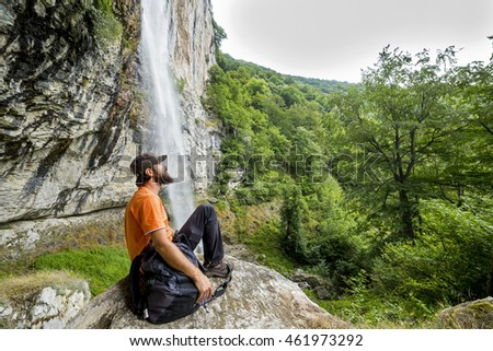 Young hiker  with backpack sitting on a rock admiring the  view