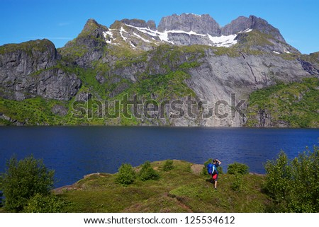 Young hiker with backpack standing by fjord on Lofoten islands in Norway on sunny day